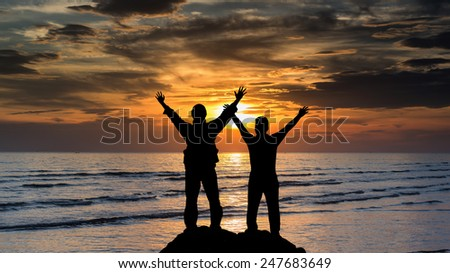 a man and boy with hands raised to beautiful Silhouette  sunset - stock photo