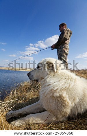 A man and his dog enjoying a day together at the lake - stock photo