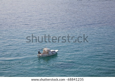 A man and his motor boat seen from above at the Adriatic Sea - Croatia. Space for text. - stock photo