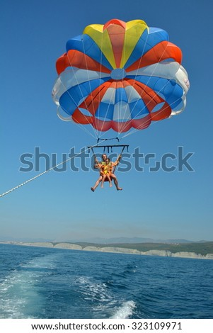 A man and his son ride on a parachute - stock photo