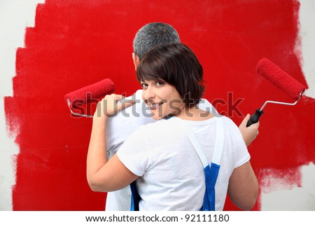 a man and his wife painting a wall - stock photo