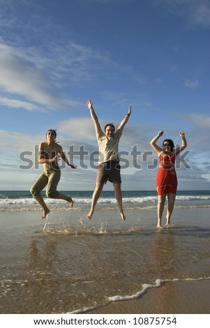 A man and two females jumping in the beach