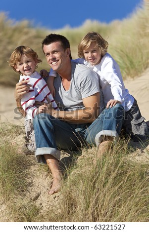 A man and two young boys, father and sons, sitting down and having fun in the sand dunes of a sunny beach