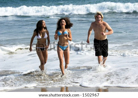 A man and two young women running from the surf at the beach