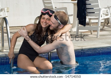 A man and woman are standing together in a pool.  They are hugging each other.  The man is looking at the woman, and the woman is looking at a camera.   Horizontally framed photo.