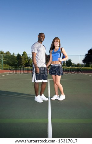 A man and woman are standing together on a tennis court.  They are smiling and looking at the camera.  Vertically framed shot.