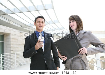 A man and woman business team at their company building