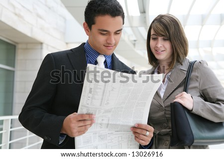 A man and woman business team at their office building reading newspaper - stock photo