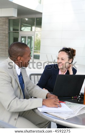 A man and woman business team communicating outside - stock photo