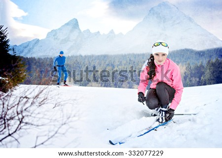 A man and woman cross-country skiing in front of winter landscape - stock photo
