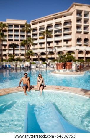 A man and woman enjoying a hotel pool with waterslide - stock photo