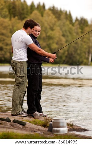 A man and woman fishing on a forest lake - stock photo