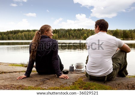 A man and woman happy camping in the forest by a lake - stock photo