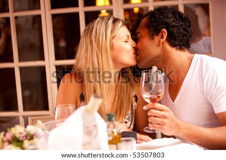 A man and woman having a romantic meal in an outdoor cafe - stock photo