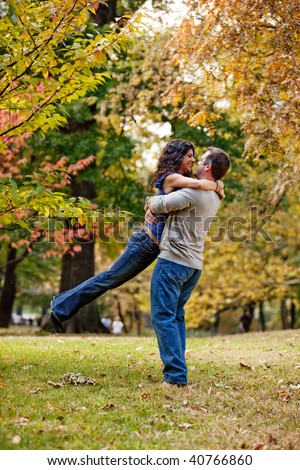 A man and woman hugging in a park - stock photo