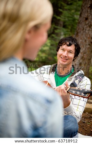 A man and woman in a forest with a guitar - stock photo