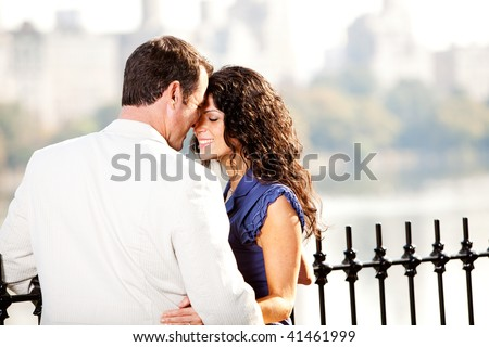 A man and woman in a park hugging
