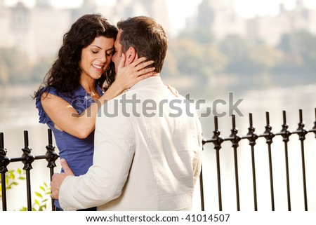 A man and woman in the park hugging - stock photo