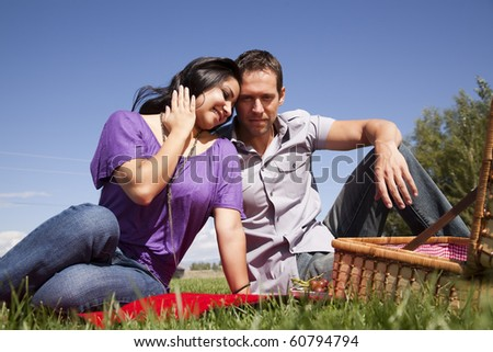 A man and woman is sitting on the grass with a picnic basket. - stock photo