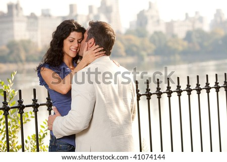 A man and woman kissing in the park - stock photo