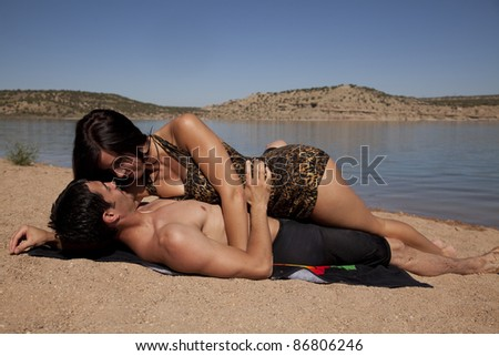 A man and woman laying on the beach together looking into each others eyes. - stock photo