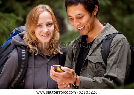 A man and woman looking at a gps in the forest - stock photo
