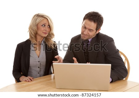 A man and woman looking at the computer screen with confused expressions on their faces.