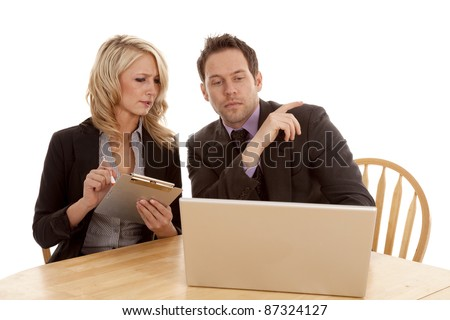 a man and woman looking at the laptop working together, the woman is taking notes.