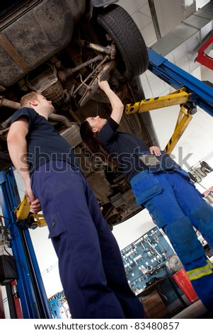 A Man and Woman mechanic looking at a car, assessing a repair - stock photo