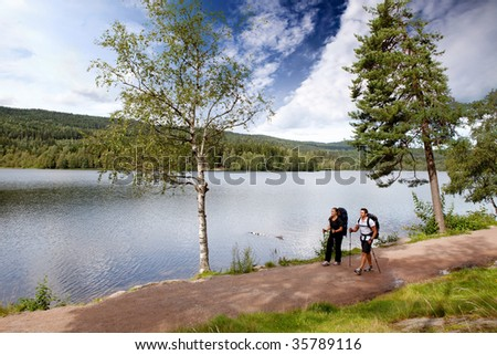 A man and woman on a hike by a lake - stock photo