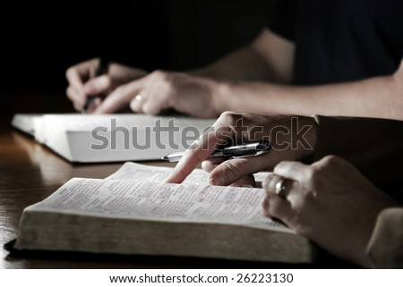 A man and woman (or married couple) study their Holy Bibles together at a table - slight color effect, shallow focus point on foreground woman's hand. - stock photo