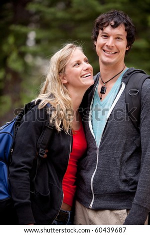A man and woman outdoors on a hike in a forest - stock photo