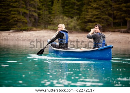 A man and woman paddling in a canoe on a lake