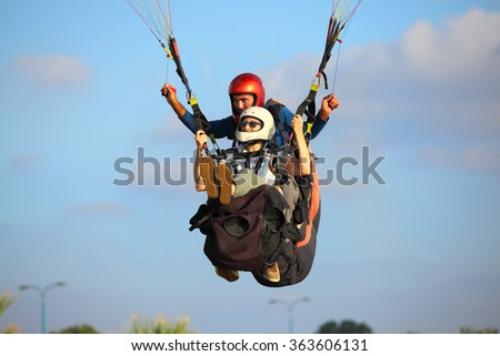 A man and woman paragliding  in the mediterranean sky - stock photo