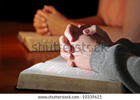 A man and woman praying together with their Bibles - male foreground hands highlighted (Christian image, shallow focus). - stock photo