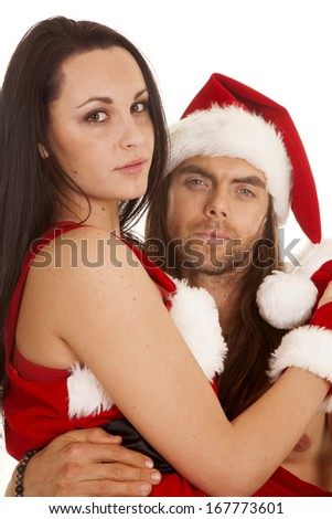 a man and woman ready for Christmas, dressed up in Santa suits and hats cuddling. - stock photo