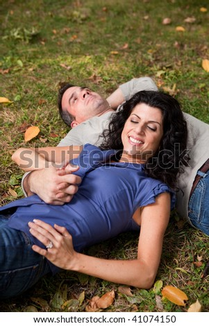A man and woman relaxing in the park laying in the grass and dreaming - focus on the woman - stock photo