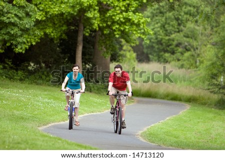 A man and woman, ride their bicycles along a park trail happily. - horizontally framed - stock photo