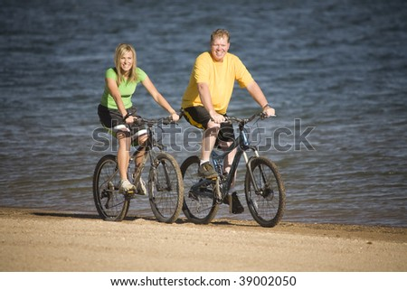 A man and woman riding bikes on the beach having fun. - stock photo