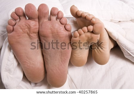 A man and woman's feet coming out of the bottom of comforter.
