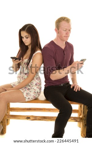 A man and woman sitting on a bench looking at their phones. - stock photo