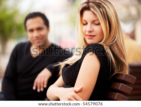 A man and woman sitting on a bench, the woman looking sky