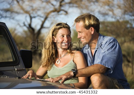 A man and woman smile at each other as they share a map spread out on the hood of a car. Horizontal format. - stock photo
