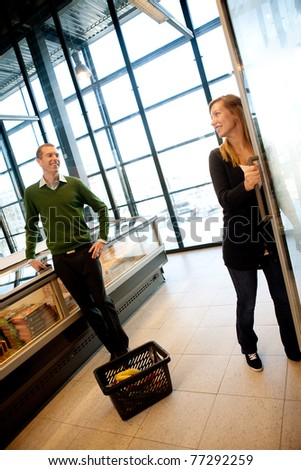 A man and woman smiling at eachother in a trendy supermarket - stock photo