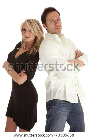 A man and woman standing back to back looking at the camera. - stock photo