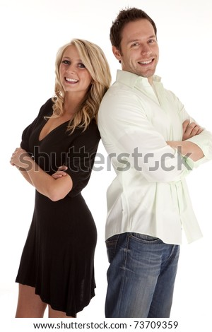 A man and woman standing back to back with smiles on their faces. - stock photo