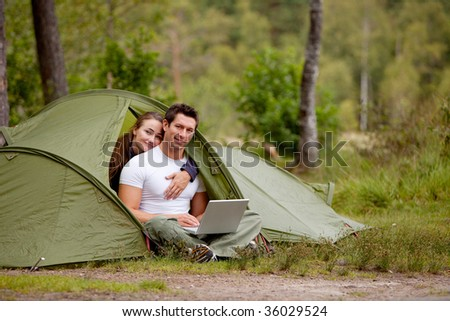 A man and woman using a computer outdoors in a tent - stock photo