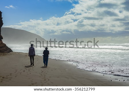 A man and woman walking along beach near Legzira in Morocco.