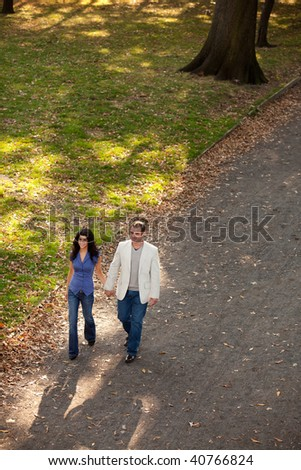 A man and woman walking in a park on a sunny day - stock photo