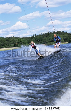 A man and woman water-skiing - stock photo